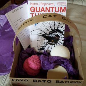 A box with a book, and bath bombs in it, with a subscription to the official Book Bath Box included