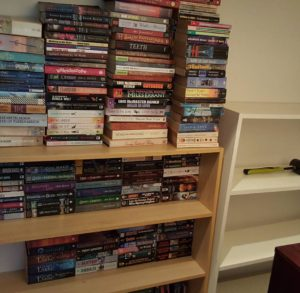 A large number of books piled onto a shelf creatively, a shelf next to that is empty.