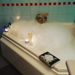 A corner bathtub filled with sparkling bubbles, surrounded by candlelight, a glass of sparkling wine, and a book on the side