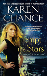 A starscape background features an attractive blonde woman in the foreground on the left hand side wearing a black dress, hands on hips looking composed with title text 'Tempt the Stars'