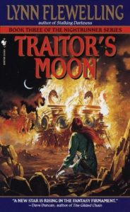 There is a burning ship with dragon mastheads in the background, there is a small male figure in the foreground with his back to the reader looking out on the ship, there are knights in the background also watching the burning shift. The title 'Traitor's Moon' is in the foreground in dark red text.