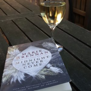 Close up cover shot of Marie Brennan's 'Midnight Never Come' with a glass of white wine with an outdoor table as background